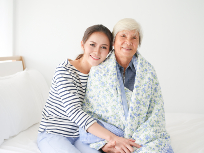 daughter with  senior woman together in bedroom
