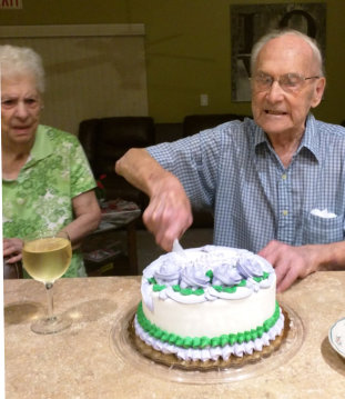 two seniors slicing a cake