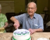 two seniors slicing a cake on the tale